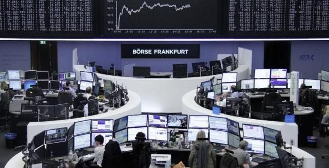 Traders work at their desks in front of the German share price index, DAX board, at the stock exchange in Frankfurt, Germany, March 1, 2016. REUTERS/Staff