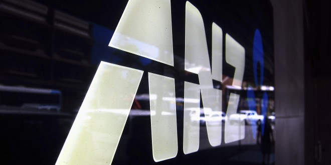 "A man is reflected in a logo for the Australia and New Zealand Banking Group Ltd (ANZ) as he walks past a branch located in a Sydney suburb February 17, 2015. ANZ on Tuesday posted a 3.5 percent rise in first-quarter cash profit, warning that 2015 was shaping up to be a ""slightly tougher, more volatile"" environment. ANZ reported cash profit of A$1.79 billion ($1.39 billion) for the three months to Dec. 31, compared with A$1.73 billion a year ago, led by a strong domestic performance, while lower trading income and higher expenses hurt revenue growth.  REUTERS/David Gray     (AUSTRALIA - Tags: BUSINESS LOGO) - RTR4PV6V"